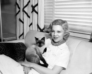 Glenda Farrell Holding Cat While Sitting on Couch